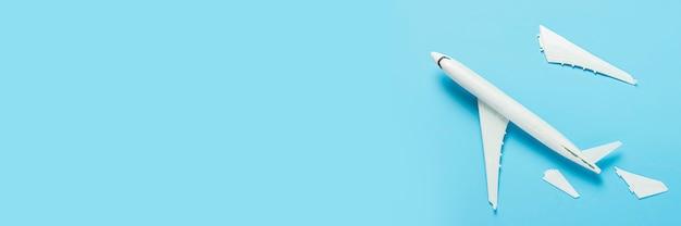 Сломанный самолет на синем фоне. концепция авиакатастрофы, неисправности. баннер