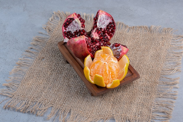 A broken pomegranate and a peeled tangerine on a piece of cloth on marble background.