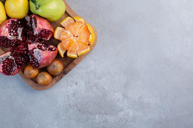 Melograno spezzato, mandarino sbucciato e mele cotogne intere su un pezzo di stoffa su fondo di marmo.