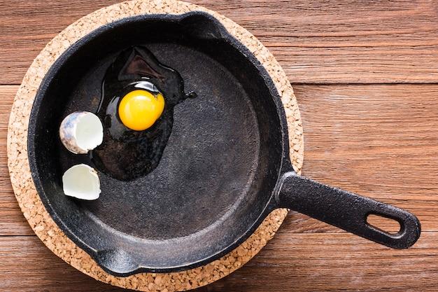 Сломанное перепелиное яйцо на сковороде на деревянном столе