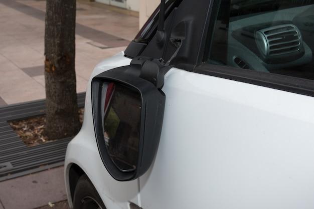 Broken rear-view mirror hanging, white car
