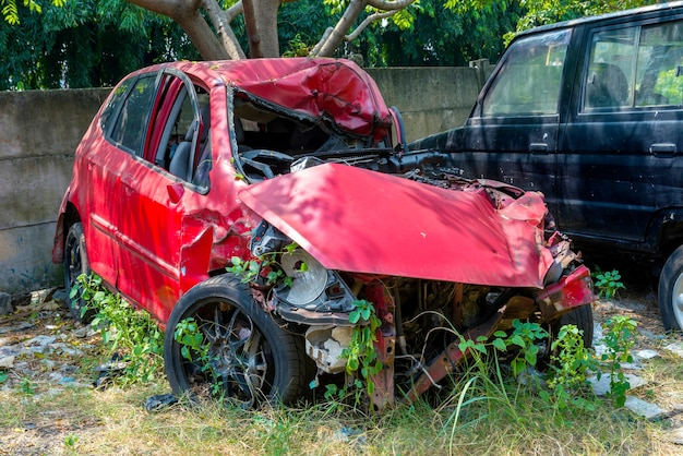 Broken red car because of the crash accident on the lawn