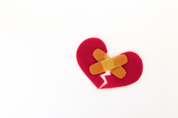 Broken red heart symbol with medical patch on white background, love concept