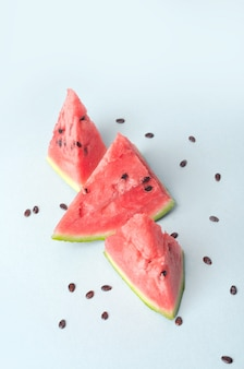 Broken red ripe watermelon with stones near it over blue surface
