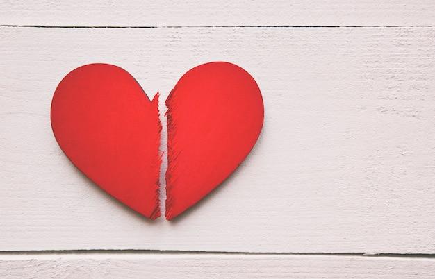 나무 테이블에 깨진 된 붉은 나무 마음. 이혼의 개념, 깨진 관계와 사랑의 끝