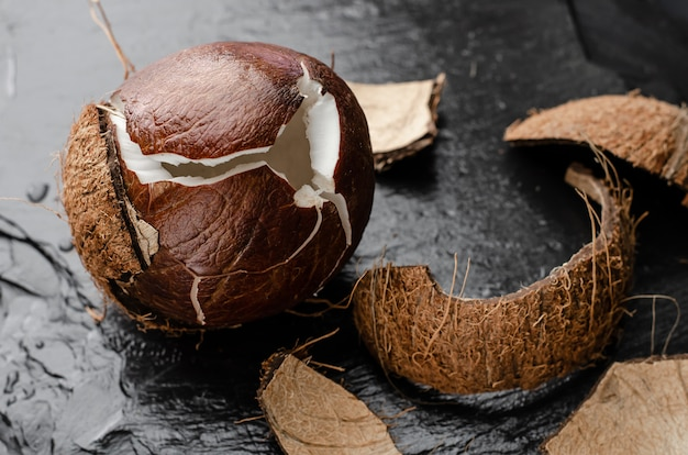 Broken ripe coconut on black slate stone background.