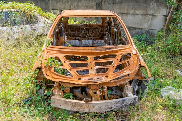 Broken rusty car because of the crash accident on the lawn