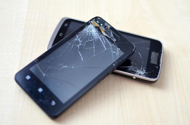 Broken screen cell phone on gray background.smartphone insurance and mobile phone warranty concept.top view. two phones