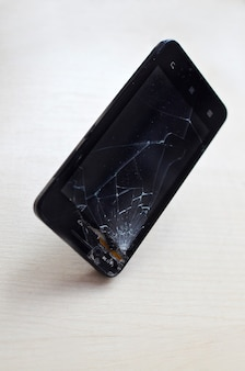Broken screen cell phone on gray background.smartphone insurance and mobile phone warranty concept.top view.