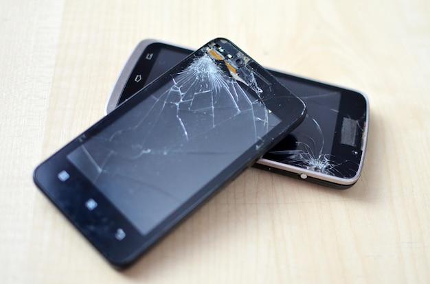Сломанный сотовый телефон экрана на серой предпосылке. концепция гарантии страхования и мобильного телефона смартфона. взгляд сверху. два телефона