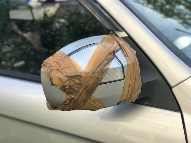 Broken side view car mirror with plastic tape