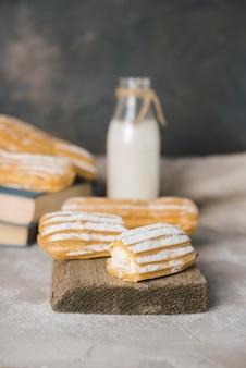 Broken slices of eclair on serving wooden board with milk bottle
