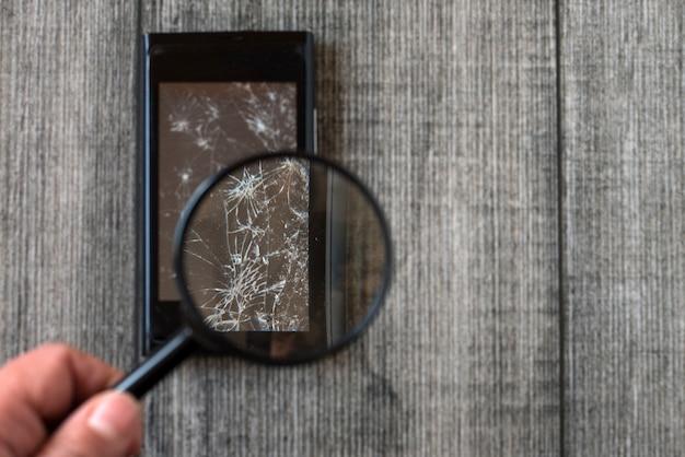 Сломанный смартфон и лупа в руке на сером деревянном фоне.