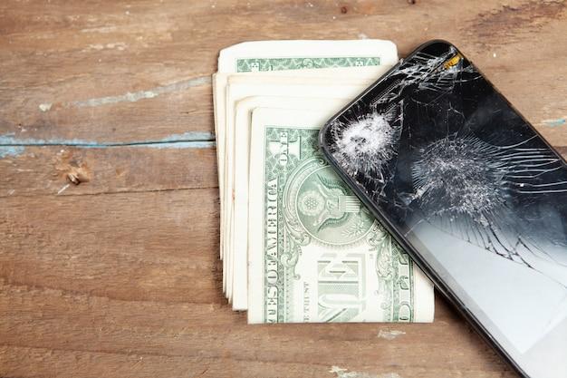 Сломанный смартфон и деньги на столе