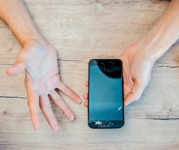Broken smartphone in the hands of a young man