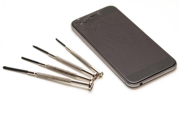 Broken smartphone and small screwdrivers for repair