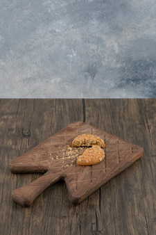 木製のまな板に壊れた甘いオートミールクッキー。