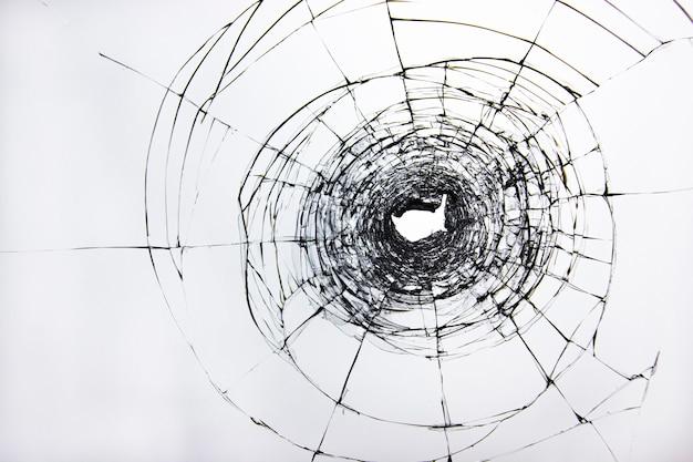문 창의 깨진 투명 유리, 파손 또는 부주의로 인해 손상된 유리에 구멍이 있습니다.