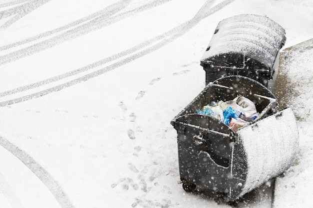 Broken trash can covered with snow. footprints and car traces on the snow near the containers. municipal economy