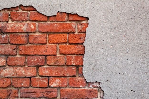Broken wall with red bricks in close-up, gray-red background, texture