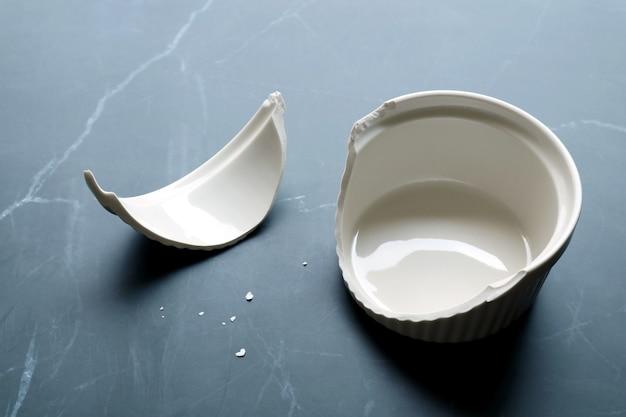 검은 대리석 주방 조리대 위에 조각이 있는 깨진 흰색 세라믹 베이킹 그릇