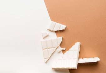Broken white chocolate bar against dual colored background