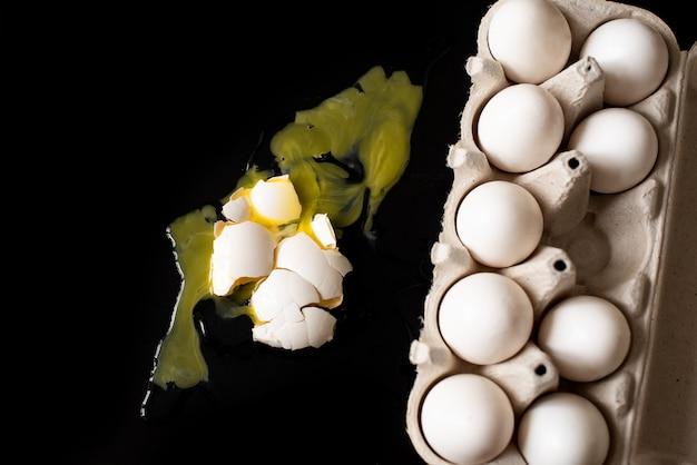 Broken white egg on black background. egg tray