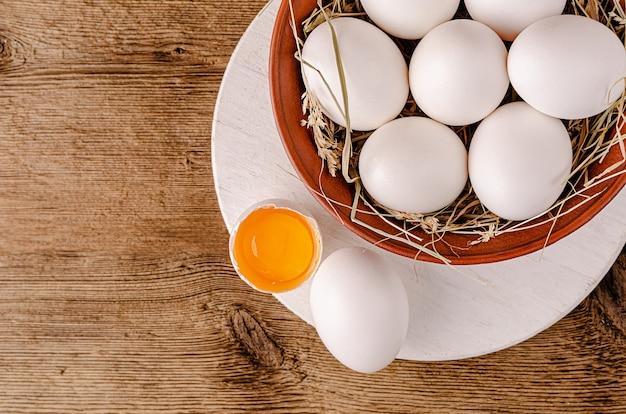 Разбитое белое яйцо с сырым желтком на деревянном фоне