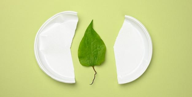 壊れた白いプラスチックプレートと緑の表面の緑の葉。プラスチックを避け、環境を保護するという概念、上面図