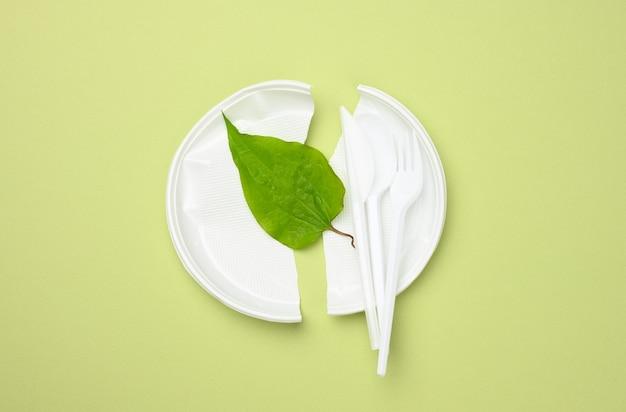 깨진 흰색 플라스틱 접시와 녹색 표면에 녹색 잎. 플라스틱을 피하고 환경을 보존하는 개념, 평면도