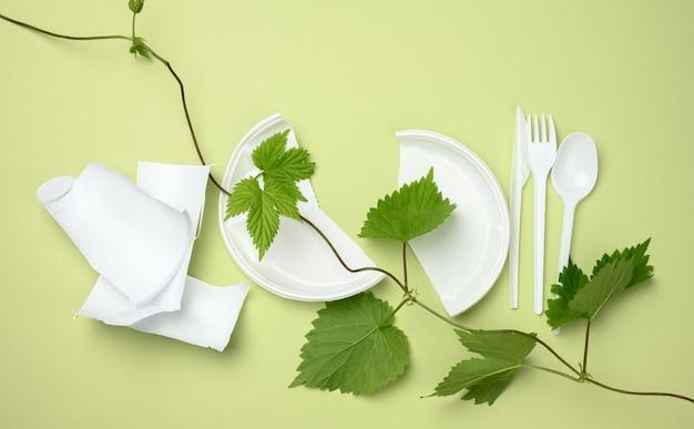 壊れた白いプラスチックのプレート、フォーク、ナイフ、枝、緑の表面に緑の葉があります。プラスチックを避け、環境を保護するという概念、上面図