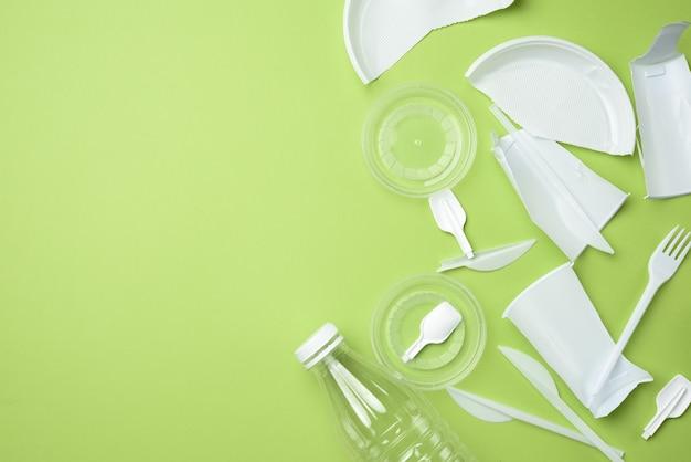Сломанная белая пластиковая посуда, прозрачная бутылка на зеленом