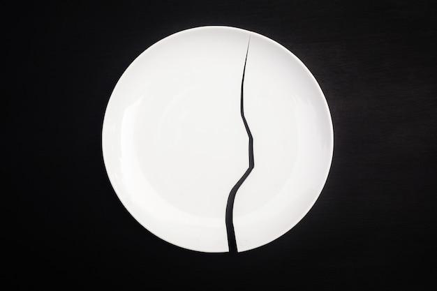검은 바탕에 깨진 된 흰색 접시