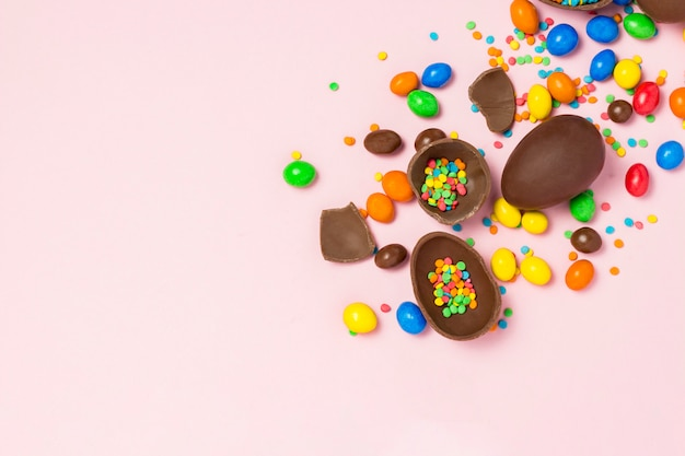 Broken and whole chocolate easter eggs, multicolored sweets, pink background. shrub. concept of celebrating easter, easter decorations. flat lay, top view. copy space. happy easter.