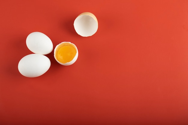 Broken and whole raw eggs on red surface.