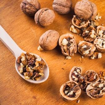 Broken; whole walnut and kernel on wooden spoon