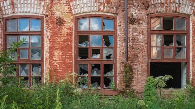 Broken windows of an old red brick building