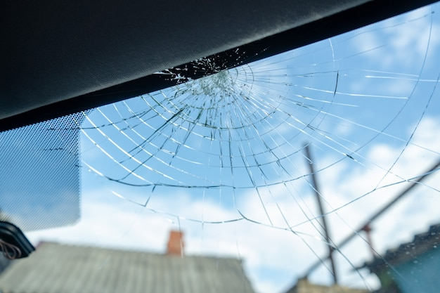 Broken windshield with a lot of cracks and small glass pieces, damaged car