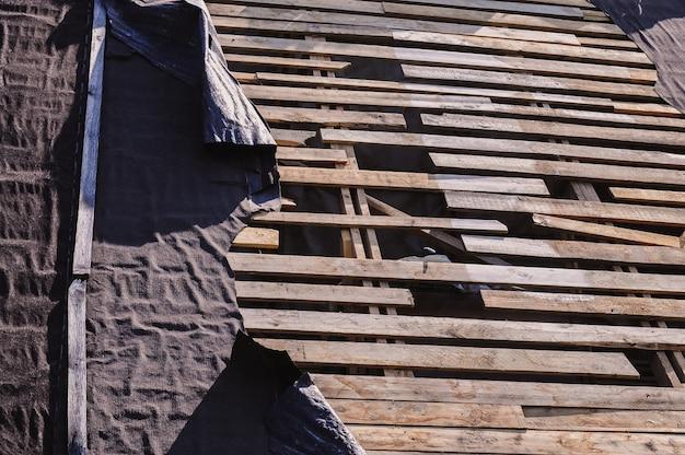 수리가 필요한 마을에 있는 오래된 집의 부러진 나무 판자 지붕과 찢어진 지붕 재료