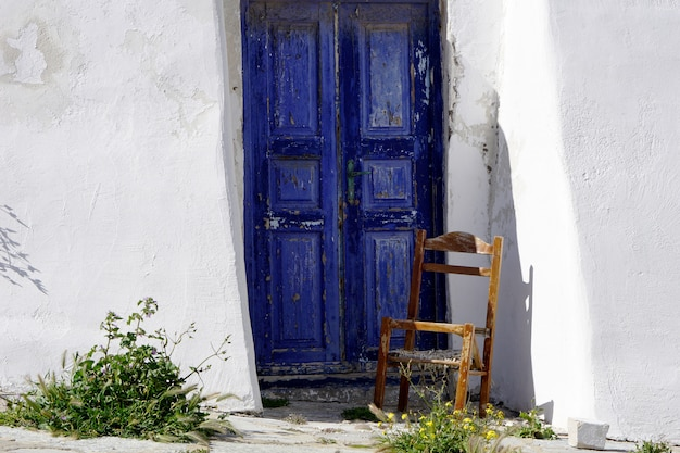 Broken wooden chair in front of the navy blue door and white wall