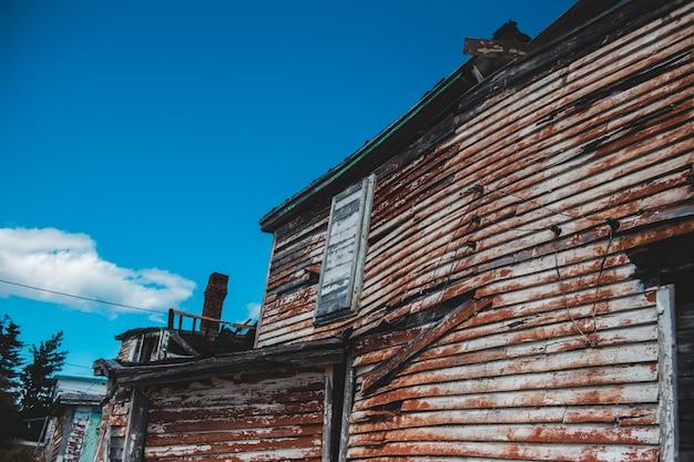 壊れた木造住宅と青い空