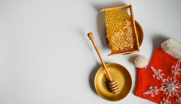 目覚まし時計の近くに蜂蜜と壊れた黄色のハニカム。上面図。フラットレイ