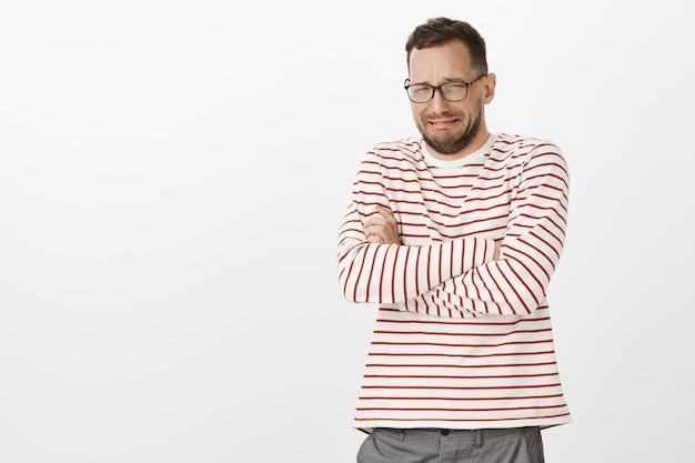 Uomo adulto miserabile dal cuore spezzato con gli occhiali, che incrocia le mani sul petto e piange, si offende o guarda l'opera di minestra