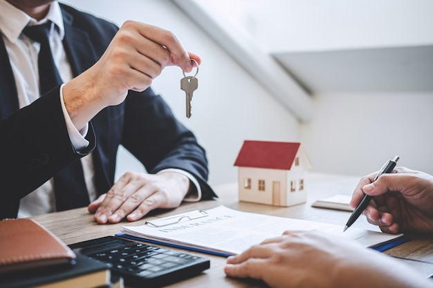 Broker agent giving house keys to client after signing agreement contract estate with approved