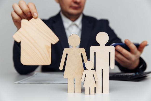 ブローカーは、住宅または住宅ローンの概念の若い家族の購入の数字の背後にある契約を承認します