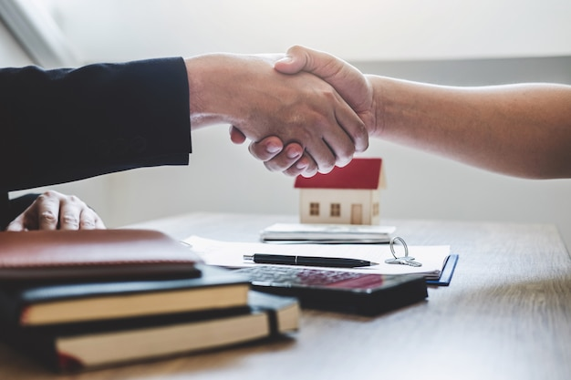 Broker and client shaking hands after signing contract