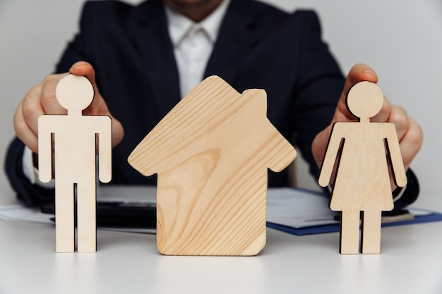 Broker holds wooden figures of young family purchase of house concept