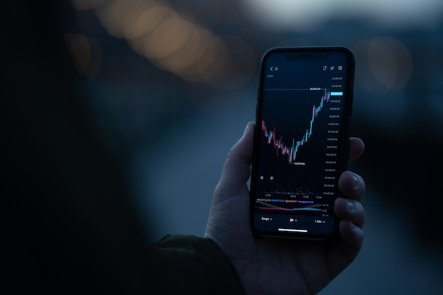 Broker or investor using stock trading app on smartphone to analyzing price flow on stock market while standing outdoors. selective focus on hand holding mobile phone with forex graph chart on screen