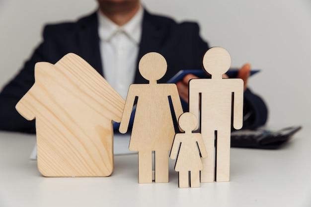 ブローカーは、家のコンセプトの若い家族の購入の数字の背後にある契約に署名します