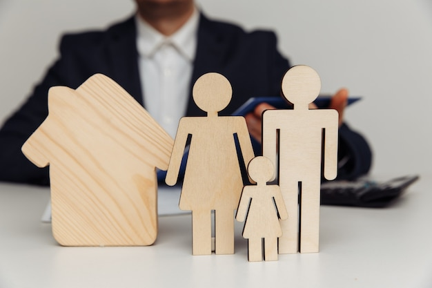 Broker signs a contract behind of figures of young family purchase of house concept